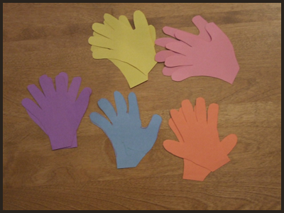 Lay Out 8 or More Colored Construction Paper Hands