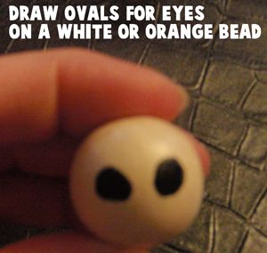 Draw ovals for eyes on a white or orange bead