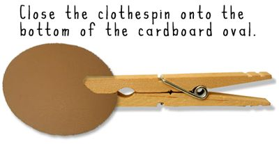 Close the clothespin onto the bottom of the cardboard oval