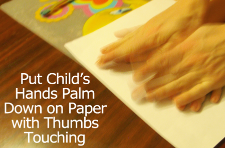 Put your child's hands, palms down, on paper with thumbs touching.