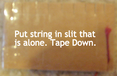 Put string in slit that is alone.