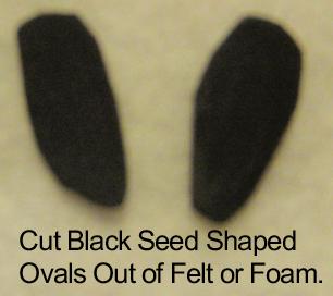 Cut black seed shaped ovals out of felt or foam