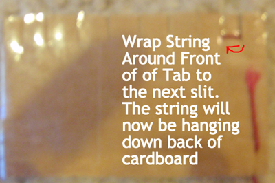 Wrap string around front of tab to the next slit.