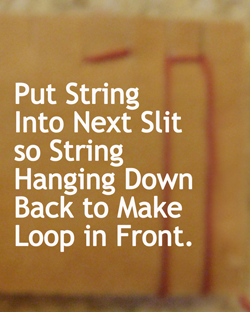 Put string into next slit so string hanging down back to make loop in front.