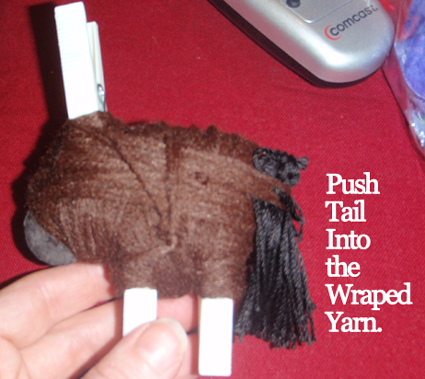 Push tail into the wrapped yarn.