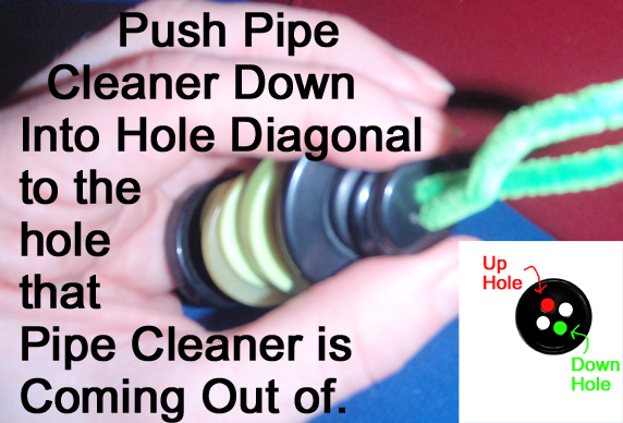 Push pipe cleaner down into hole diagonal to the hole that the pipe cleaner is coming out of.