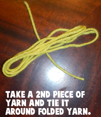 Take a 2nd piece of yarn and tie it around folded yarn.