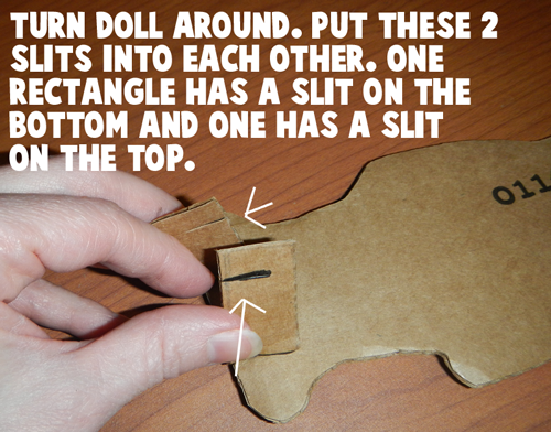 Turn doll around.  Put these two slits into each other.
