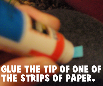 Add glue to the tip of one of the strips of paper.