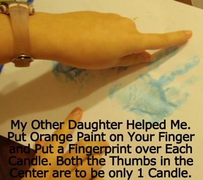 Put orange paint on your finger and put a fingerprint over each candle.