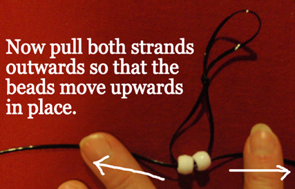 pull both strands outwards so that the beads move upwards in place.