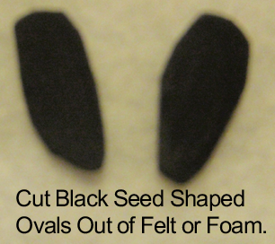 Cut black seed shaped ovals out of felt or foam