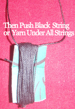 Then push black string or yarn under all strings.