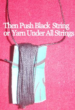 Then push black string or yarn under all strings.
