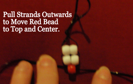 Pull strands outwards to move red bead to top and center.