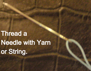 Thread a needle with yarn or string.