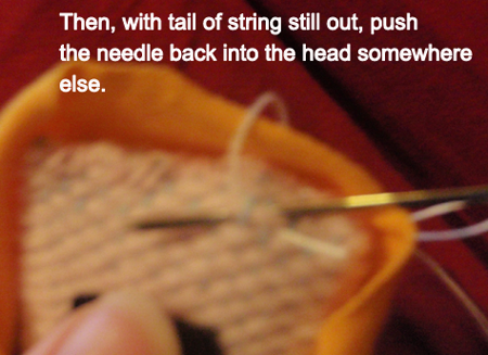 with tail of string still out, push the needle back into the head somewhere else.