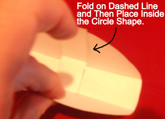 Fold on dashed line and then place inside the circle shape.