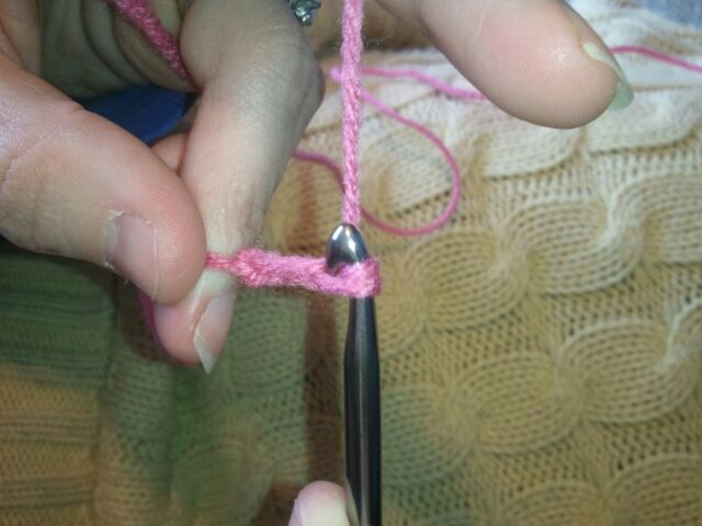 grab a hold of the yarn and pull it through the loop on the crochet hook.