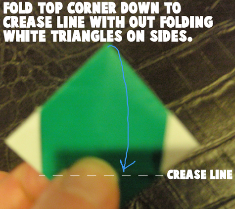 Fold top corner down to crease line without folding white triangles on sides.