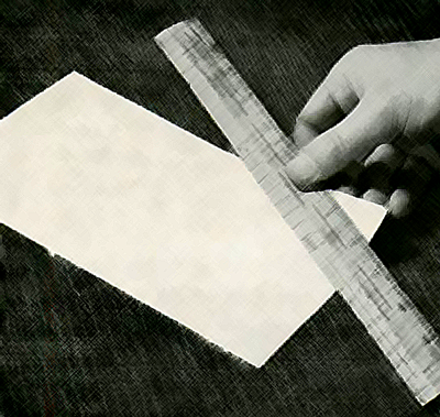 Cut a strip of paper, hold the ruler firmly across it and pull it through and upwards.