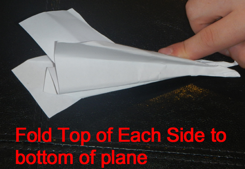 Fold top of each side to bottom of plane.