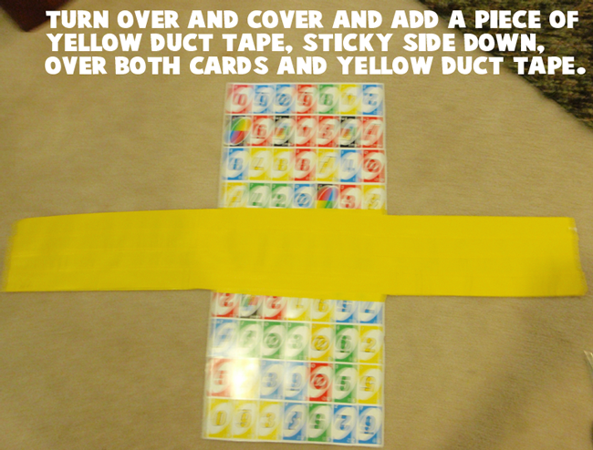 Turn over and cover and add a piece of yellow duct tape, sticky side down, over both cards and yellow duct tape.
