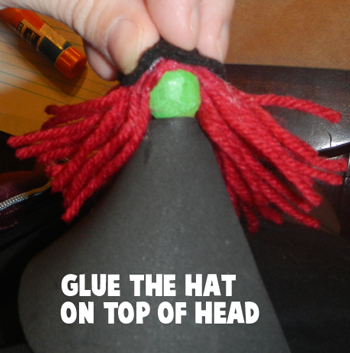 Glue the hat on top of head.