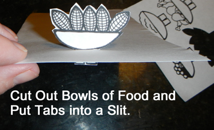 Cut out bowls of food and put tabs into slit.