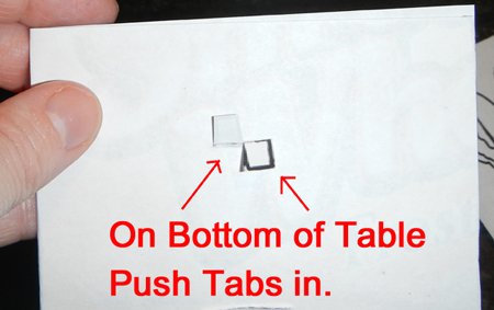 On bottom of table push tabs in.