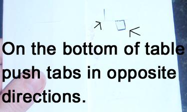On the bottom of table push tabs in opposite directions.
