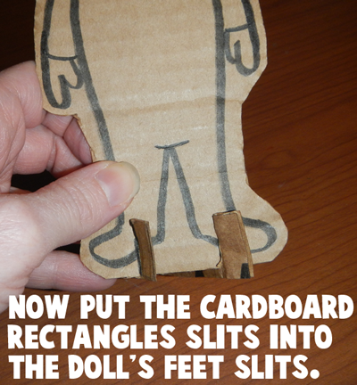 Now put the cardboard rectangle's slits into the doll's feet slits.
